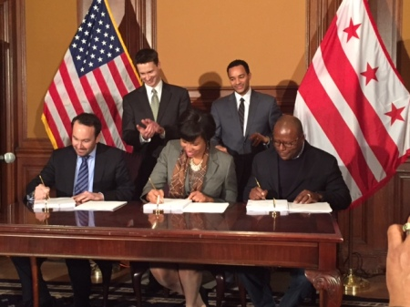 Mayor Bowser signs the Res. 13/Hill East LDA with Chris Donatelli of Donatelli Development (to her left) and Scottie Irving of Blue Skye Construction (to her right) while Ward 6 Councilmember Charles Allen and Deputy Mayor Brian Kenner look on.